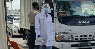 PERIKSA: Salah satu mahasiswa AKAFARMA PIM bersama petugas melakukan pengecekan kepada supir truk di pos check point.